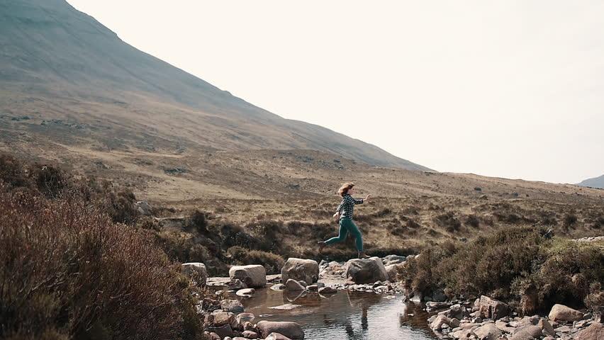 Woman Leaping across River Rocks | Shutterstock HD Video #1007680690