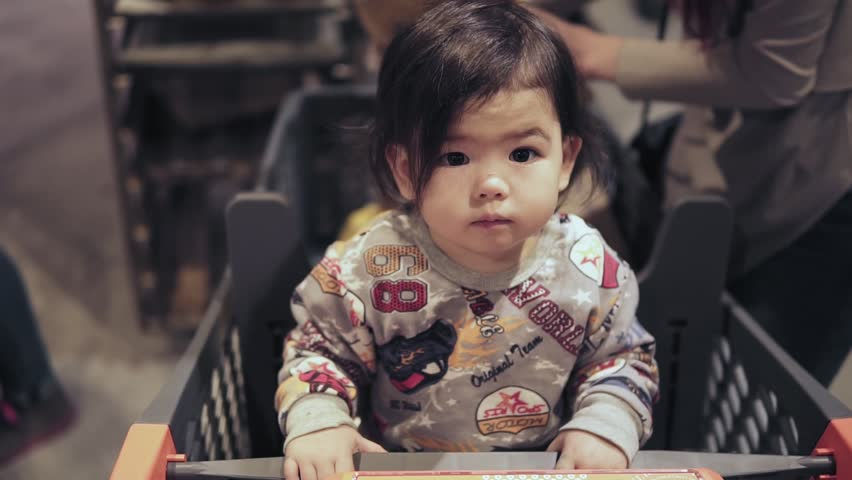 Cute asian toddler boy is sitting in a shopping cart while his mom is picking out groceries at supermarket. | Shutterstock HD Video #1007682130