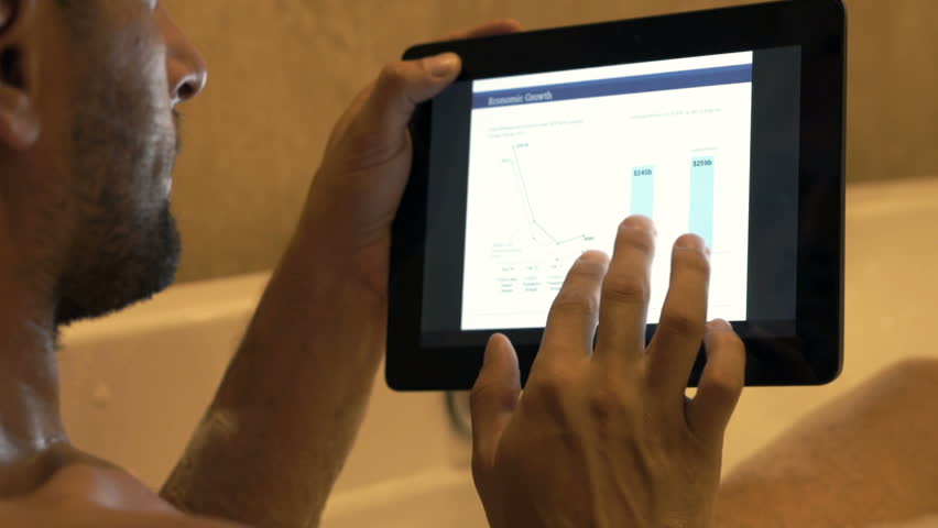 Young man checking corporate graphs on tablet during bath   | Shutterstock HD Video #1007685988