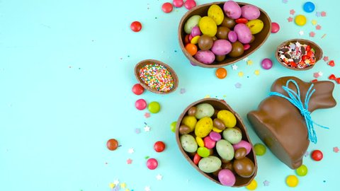 Happy Easter decadent chocolate background overhead with Easter eggs and candy on a rustic wood background with copy space.
