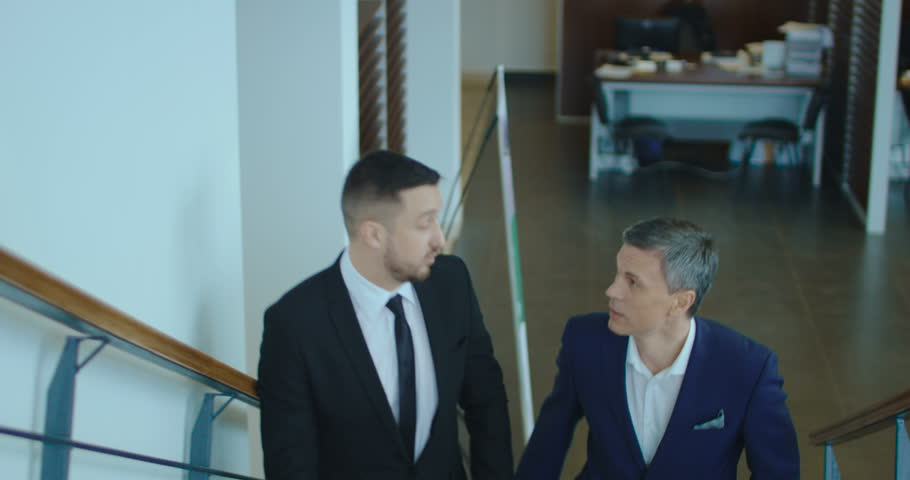 Two adult businessmen in suits go up the stairs and emotionally talk.