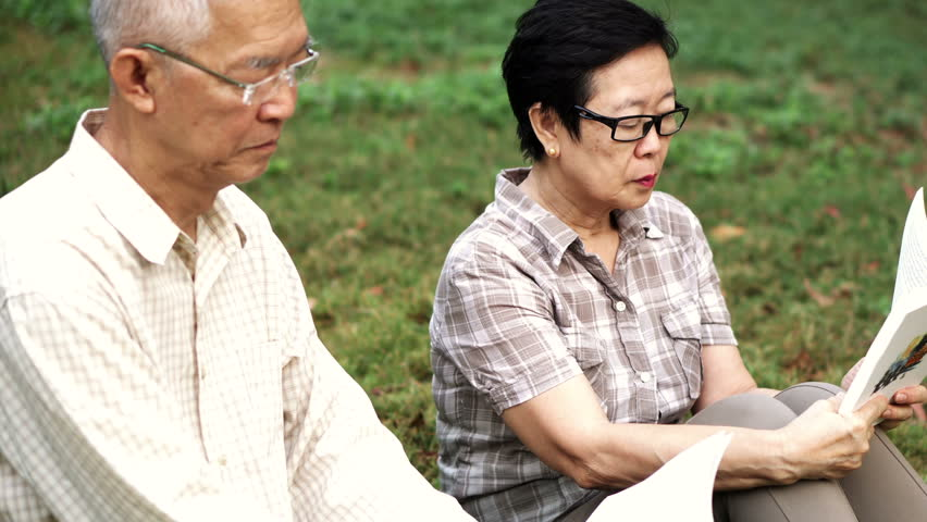 Asian senior couple reading books in park. Leisure outdoor activity