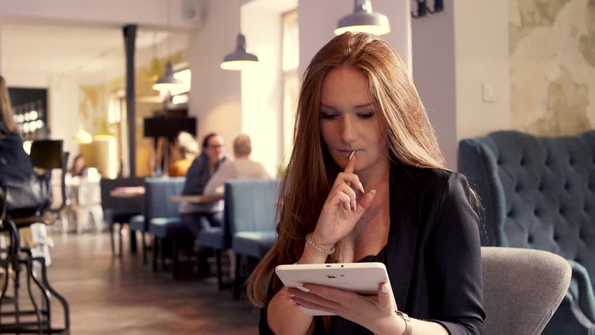 Young beautiful businesswoman sitting withn tablet in cafe | Shutterstock HD Video #1007703370