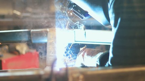 A welder working on steel. A smooth movimento to the side, lika a dolly