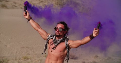 Man in steampunk style holding smoke bombs and standing in desert partying at music festival