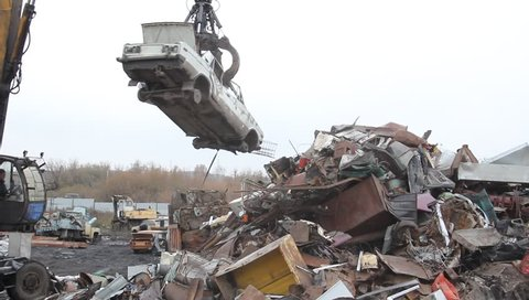 Sorting and loading of scrap metal/Excavator is loading scrap metal junk into a bin at a garbage dump or recycling center.
