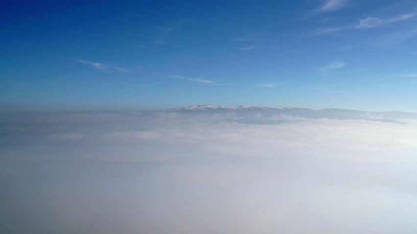 Cinematic 8K resolution 7680x4320 30p. Snowy hill over the clouds. There is a antenna on the summit of the mountain. Everywhere in the winter season covered with fog and clouds. Time lapse footage.