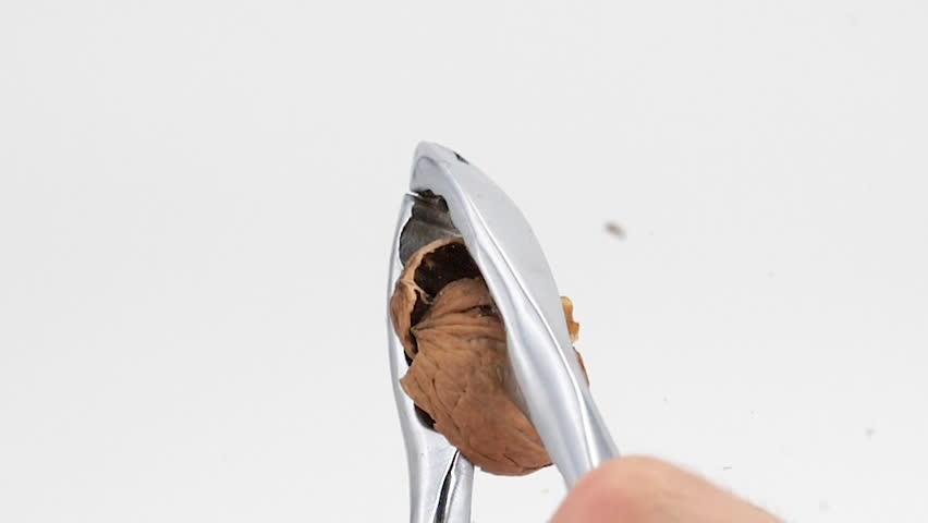 Broken walnut with nutcracker on a white background, slow-motion