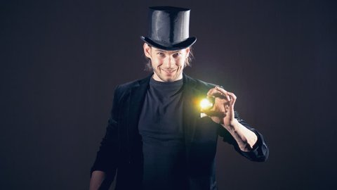 Magician is making a sparkling crystal disappear from his right fist and taking from the air.
