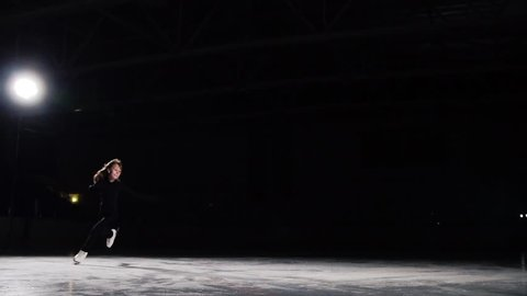 A professional figure skater performs ice skating with a jump in the air with a black background in a black suit. Slow motion.