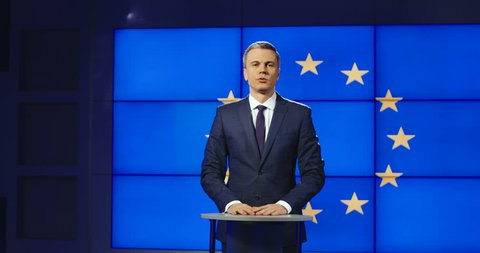 Smart male news anchor presenting European news standing in front of the EU flag speaking panning slowly to the left? Shot on Red cinema camera.