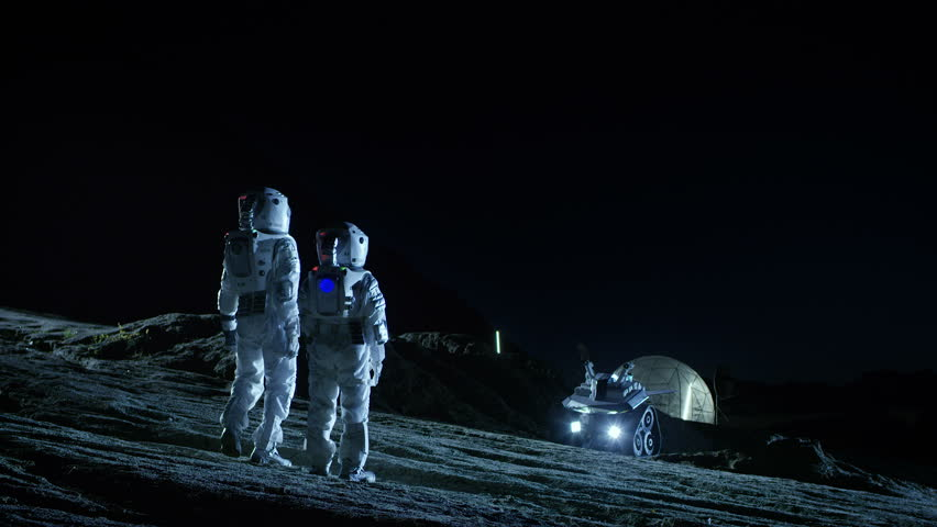 Two Astronauts in Space Suits Walk on the Alien Planet Looking at the Sky. In the Background Base with Geodesic Dome. Other Worlds Colonization and Space Travel Concept. Shot on RED EPIC-W 8K Camera.