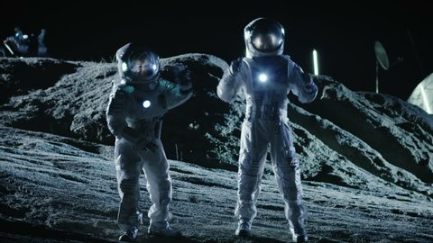 Male and Female Astronauts Wearing Space Suits Dance on the Surface of the Alien Planet. Humanity Colonizing Space Celebration Theme. Shot on RED EPIC-W 8K Helium Cinema Camera.
