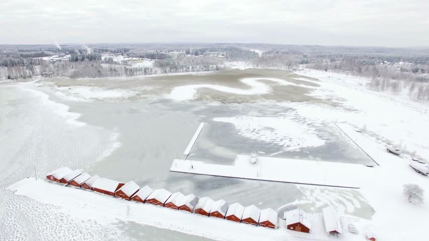 Aerial shot of a frozen bay with wooden red boathouses of the local harbour in Kerimaki, Finland.