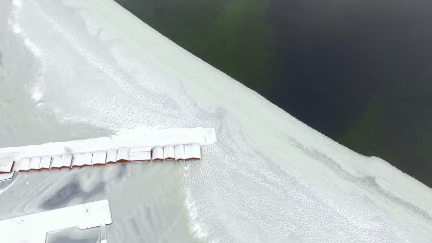 Aerial top-down view of boathouses at snowy partly frozen lake near edge of open water.