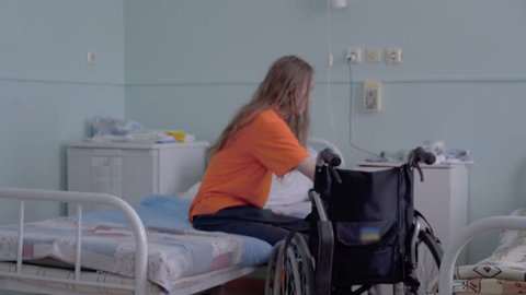 Young guy, a disabled person with a lesion of the spinal cord and legs, multiple sclerosis, without assistance, is transplanted from a hospital bed to a wheelchair.