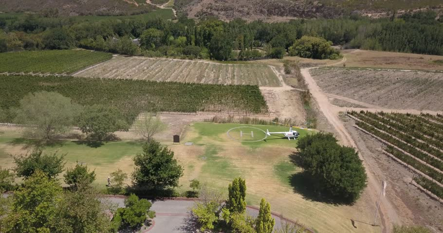 4K summer day aerial video view a helicopter landing in private heliport in Lanzerac's Western Cape's Stellenbosch wine estates area and grape plantations in background near Cape Town, South Africa