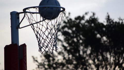 A Close Up Shot of a Netball Hoop and Net with a Netball being successfully shot into the goal. A Golden Hour setting with the clouds and trees blurred in the background.