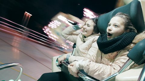 Beautiful sisters ride a spinning attraction in an amusement park. Young women are dancing at an attraction.
