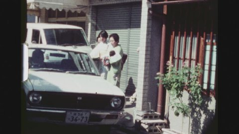 KYOTO, JAPAN, APRIL 1978. Street Shot Of Three Traditionally Dressed Japanese Women With A Baby In Arm Getting Ready To Enter A Parked Car.