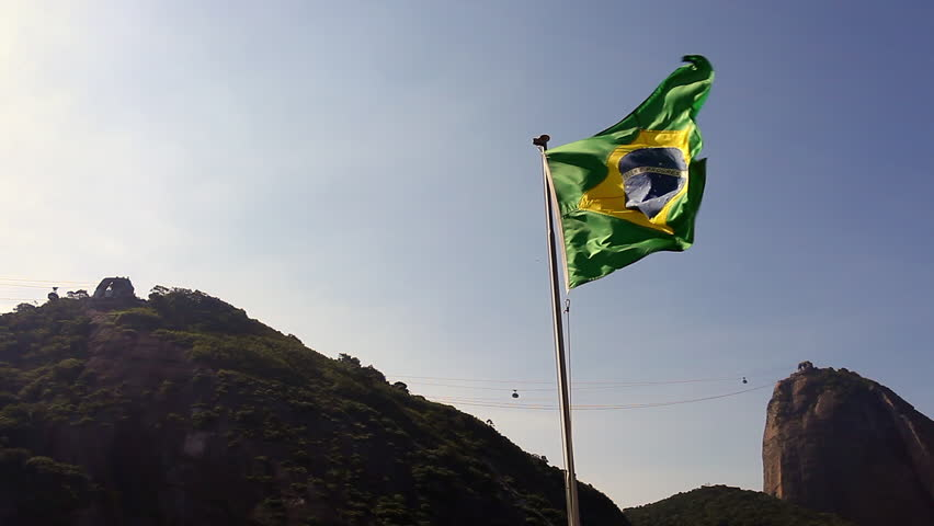Brazilian flag at Red Beach (Praia Vermelha) in front of a bright afternoon view of Sugarloaf Mountain (Pao de Acucar) at Urca in Rio de Janeiro, Brazil