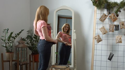 Charming smiling redhead adult woman admiring her body shape after weight loss while standing in front of mirror at home. Reflection in the mirror of cheerful female in old jeans after successful diet