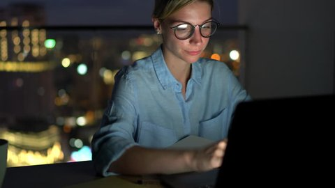 Smiling attractive female in eye glasses with reflection of screen lights reading news on smartphone in social network and using laptop computer while sitting at night with darkness in home interior