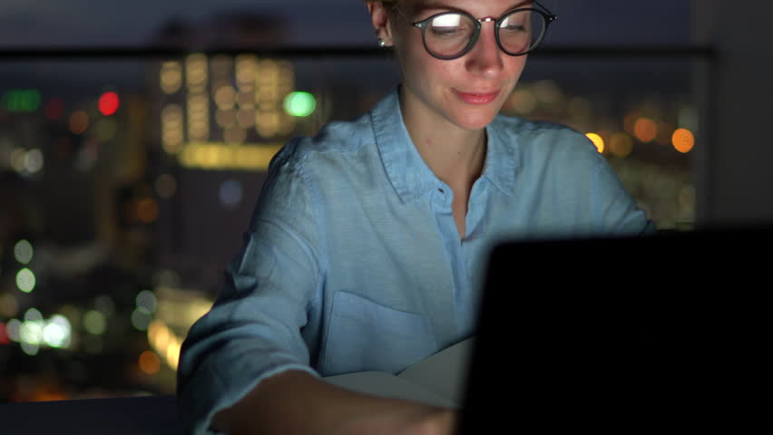 Smiling attractive female in eye glasses with reflection of screen lights reading news on smartphone in social network and using laptop computer while sitting at night with darkness in home interior | Shutterstock HD Video #1007840560