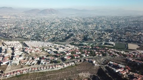 Aerial footage of a residential area in Tijuana, Baja California, Mexico during a Santana, local name for sand storm. High density of houses in a desert area, dusty sky.