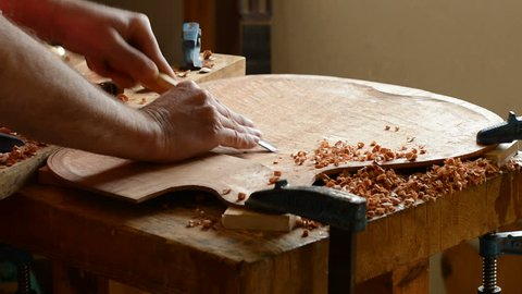 Luthier carving a guitar cover with a gouge in the workshop