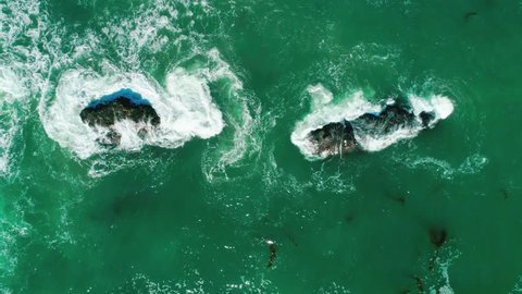 Oceanic waves are broken up into rocks. View from the top. Malibu, California.