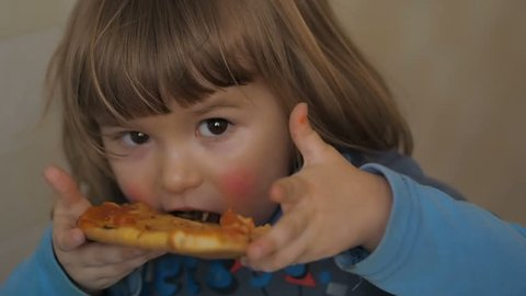 Cute little Caucasian boy eating pizza. Hungry child taking a bite from pizza.