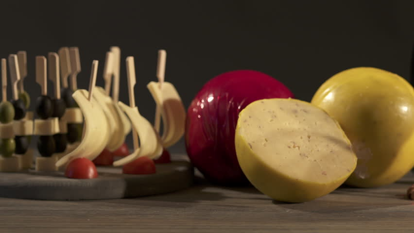 Edam cheese and wine tasting. Two glasses with red wine, grapes and cheese skewers on wooden table on a dark background. Dolly shot