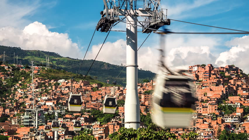 Medellin, Colombia, time lapse view of the iconic Metrocable (cable car) system over Comuna 13 slums during daytime. Dolly left to right.