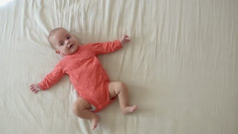 Cute little baby girl lying on the bed in pink body
