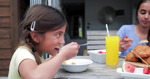 Side angle view of a little girl eating cornflakes outside while on holiday with her family.