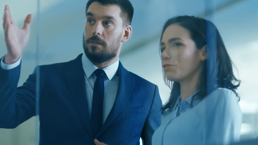 Top Manager and Female Executive Discuss Term's of Company Optimization Plan while Standing in the Modern Glass and Concrete Office. Shot on RED EPIC-W 8K Helium Cinema Camera.