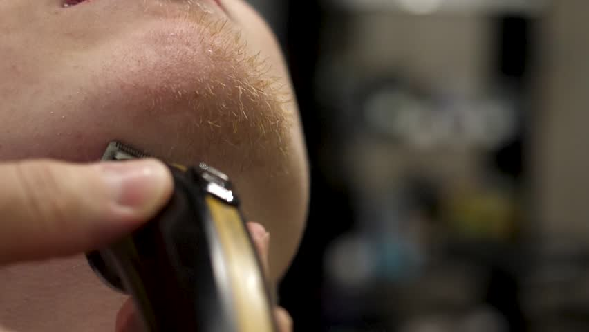 Close-up side view portrait of young bearded man getting beard grooming in modern barbershop in slow motion. Hairdresser serving client, making beard haircut using shaver. Take care of you beard