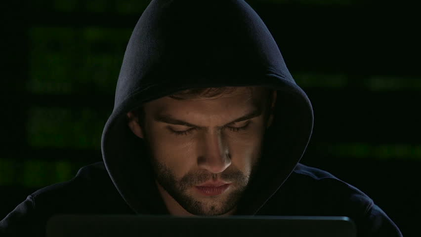 Hacker in hood illegally hacking site selecting passwords, access is allowed
