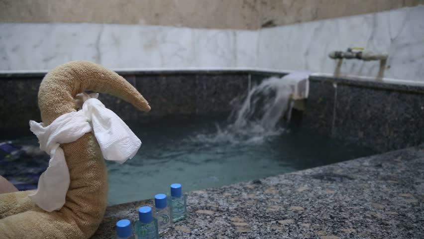 A young man having a rest and enjoying the turkish bath with lots of foam , Turkish hamam in spa salon , konya ?lg?n bath