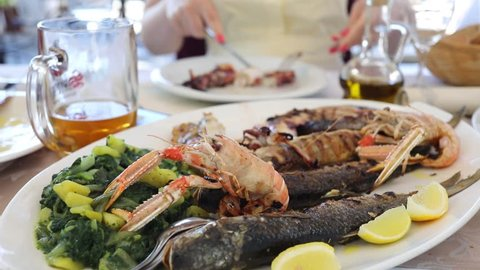 Dish with fish and seafood on the table in restaurant, woman out of focus, noface