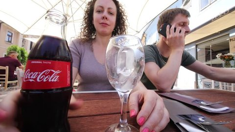 ZAGREB, CROATIA - MAY 19, 2017: (slow motion) Woman pours Coca-Cola and man drinks Coca-Cola (pair with MR), Coca-Cola was recognized as most expensive brand in world in 2005-2015