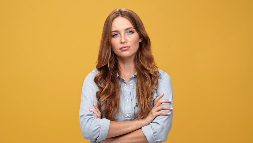 Bored ginger woman in denim shirt posing with crossed arms and looking at the camera over yellow background