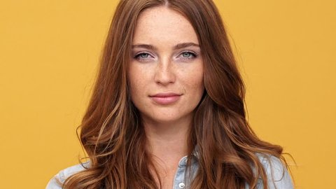 Close up of Smiling ginger woman in denim shirt keep secret and looking at the camera over yellow background