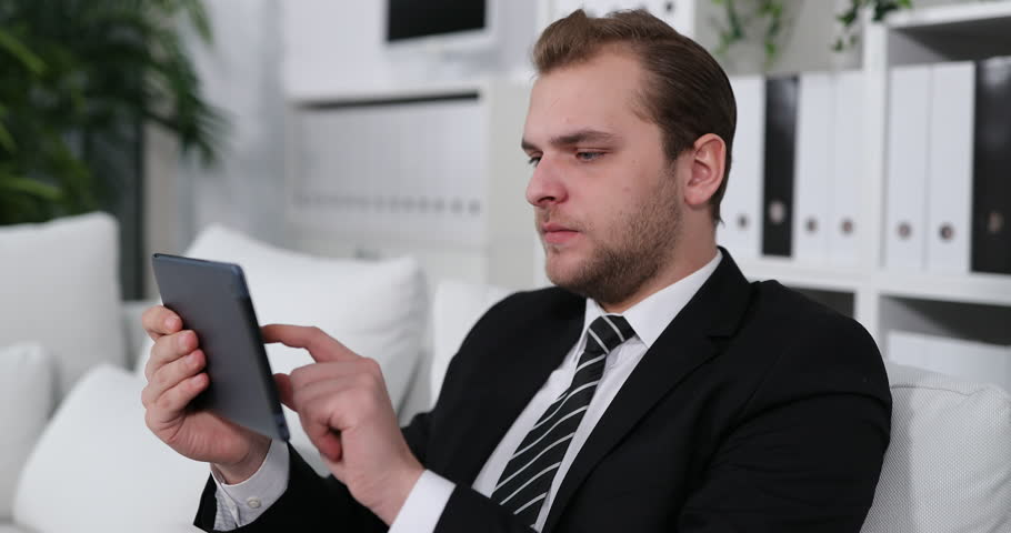Upset Business Man Suffer from Head Pain While Working on Digital Tablet on Sofa | Shutterstock HD Video #1008039910
