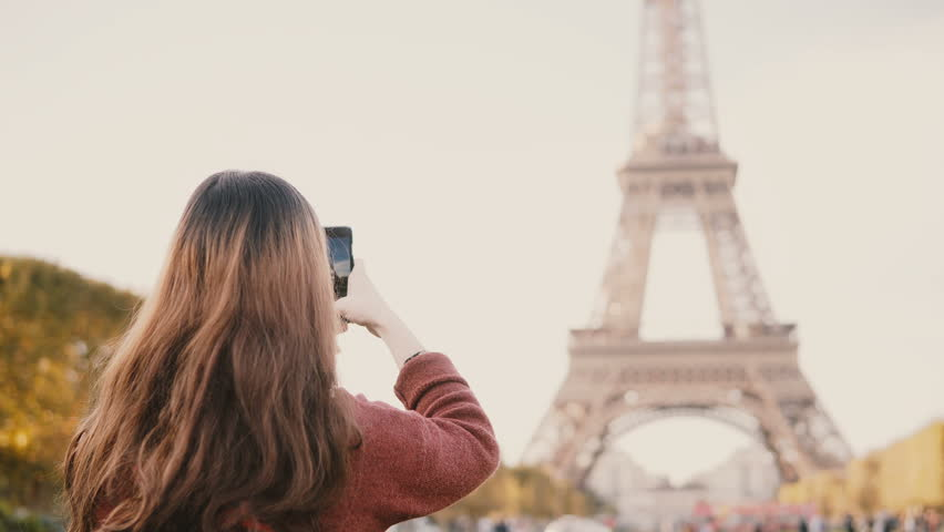 Back view of young brunette female taking photos of Eiffel tower on smartphone. Teenager exploring Paris, France. | Shutterstock HD Video #1008067090