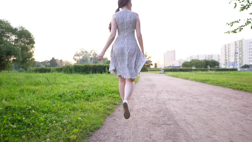Young adult woman in light summer dress walk at city park path, POV camera follow behind. Empty gravel path, girl leisurely stroll ahead, green grass and some trees seen around