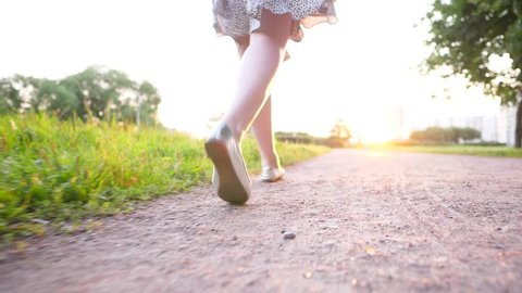 Slender young adult woman stroll in sunny evening at park, low legs tracking camera, slow motion shot. Silver flat shoes and light summer dress skirt, Beautiful natural low sun light at evening time