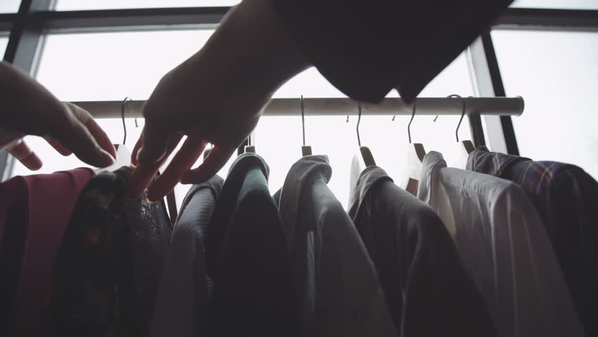 Close-up of female hands plucked a hanger with clothes. Woman's hands run across a rack of clothes. Dolly shot from the side. Woman's hand smoothing a colorful clothes. Close-up: a hanger for clothing | Shutterstock HD Video #1008076780