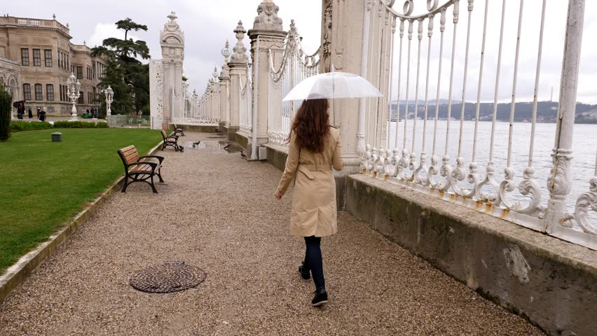 Pensive tourist woman stroll along old iron-cast fence at Bosphorus strait embankment, Dolmabahce Palace park at waterfront. POV camera follow behind, lady hold umbrella, light rain at autumn day